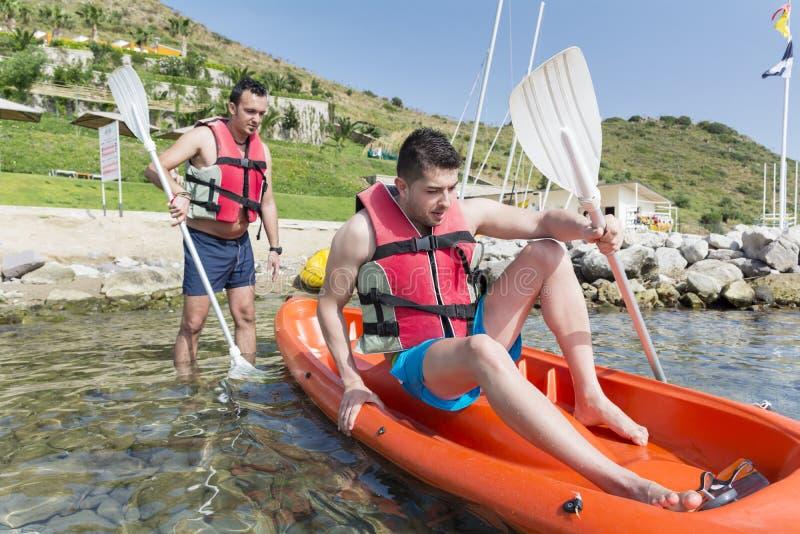 Dois amigos novos que ejoying as férias, indo no mar com canoa amarela fotos de stock