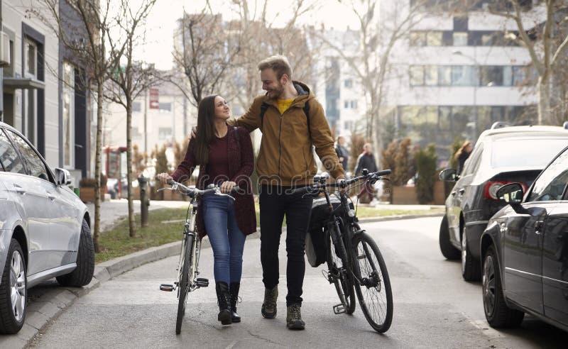 Dois amigos ou pares, 20-29 anos, andando e falando em uma rua, empurrando suas bicicletas, olhando se imagens de stock