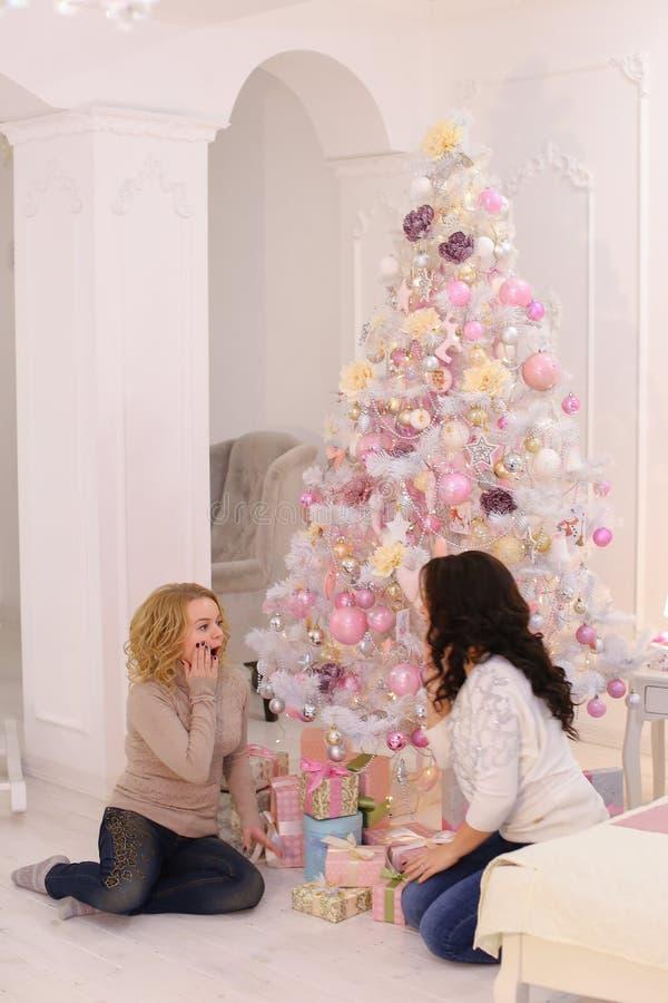 Dois amigos próximos compartilham de emoções agradáveis e os presentes festivos, sentam-se fotos de stock royalty free