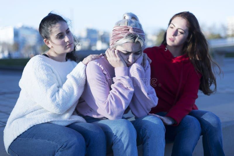 Dois amigos que cheering acima da menina deprimida nova fora fotos de stock royalty free