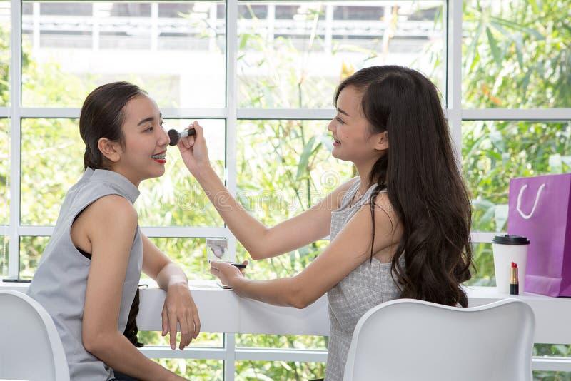 Dois amigos que compõem no café Mulher bonita nova com escova da composição fotografia de stock
