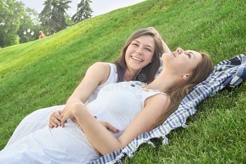 Dois amigos que encontram-se na grama no parque fotos de stock royalty free