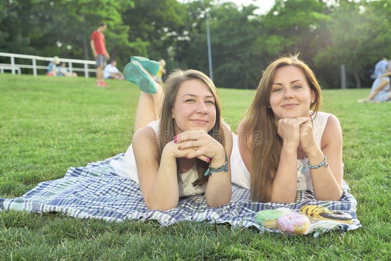 Dois amigos que encontram-se no gramado fotografia de stock royalty free