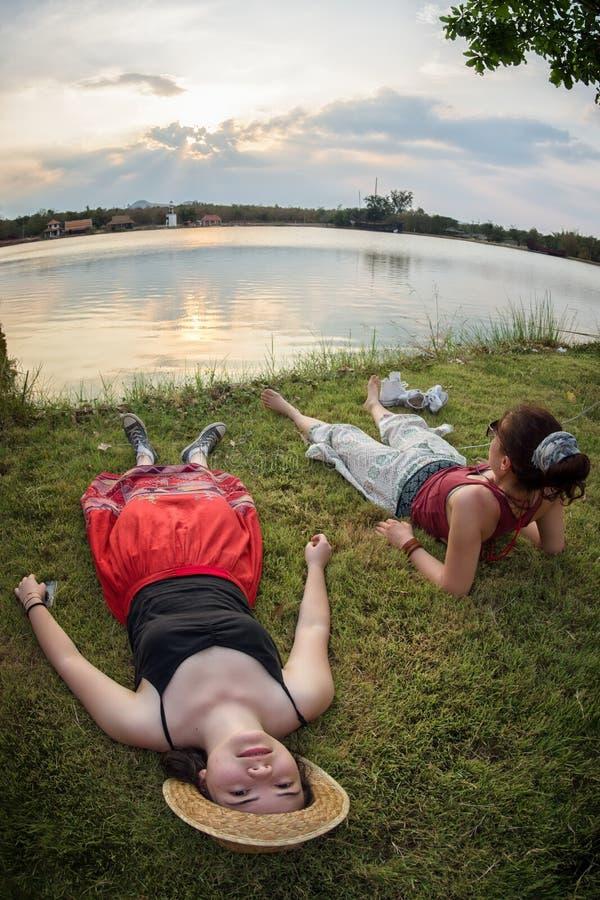 Dois amigos que refrigeram pelo lago imagens de stock royalty free