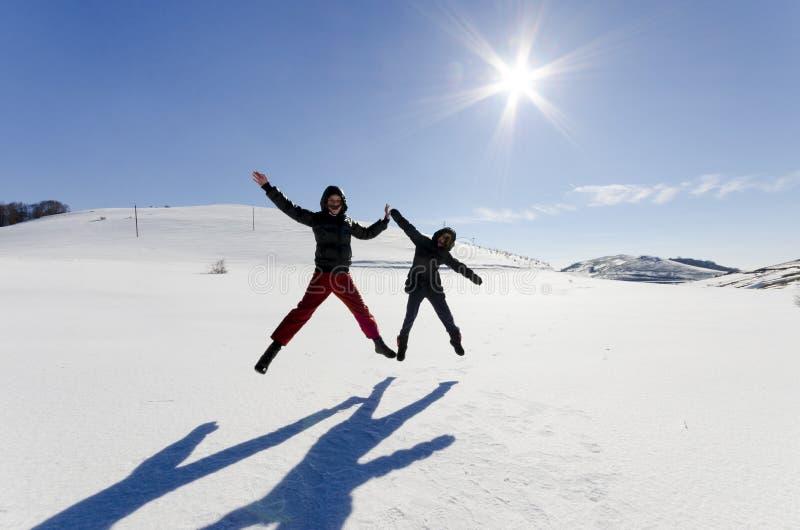 Dois amigos saltam alegremente no céu sobre a neve fotografia de stock
