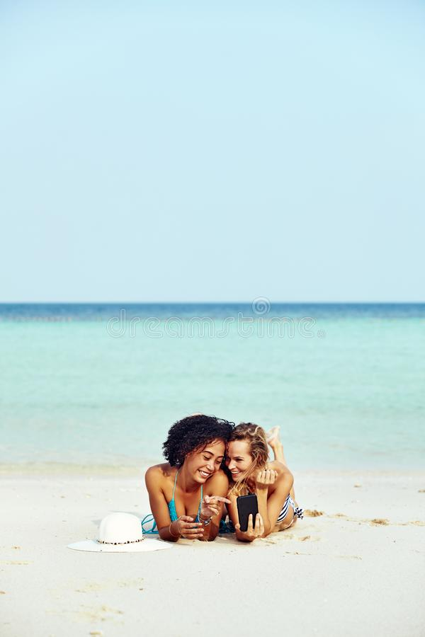 Dois amigos suntanning que olham fotos do telefone celular em uma praia fotos de stock