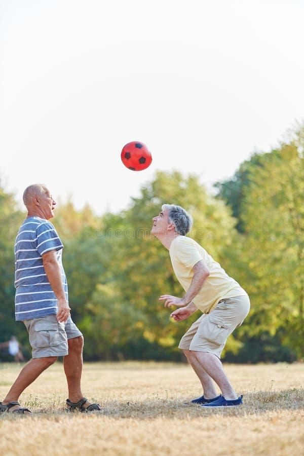 Dois amigos superiores ativos que jogam o futebol fotografia de stock royalty free