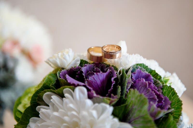Dois anéis dourados em um ramalhete do casamento fotos de stock royalty free