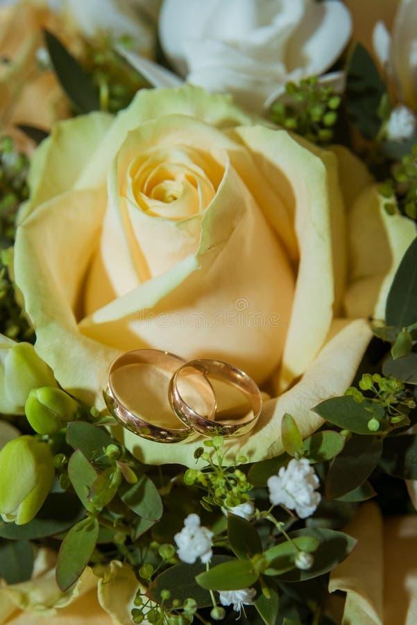 Dois aneis de noivado do ouro em uma rosa amarela do ramalhete do ` s da noiva fotos de stock royalty free