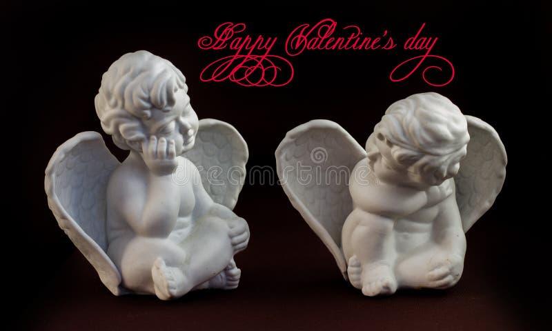 Dois anjos de pedra pequenos que sentam-se oposto a se fotos de stock royalty free