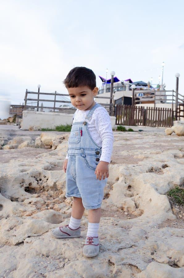 Dois anos bonitos do menino idoso que joga nas rochas na frente das casas de barco em malta imagens de stock royalty free