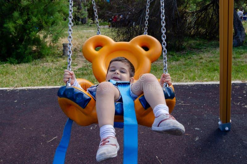 Dois anos bonitos do playig velho do menino no ar livre do campo de jogos das crian?as no balan?o do urso de peluche fotografia de stock