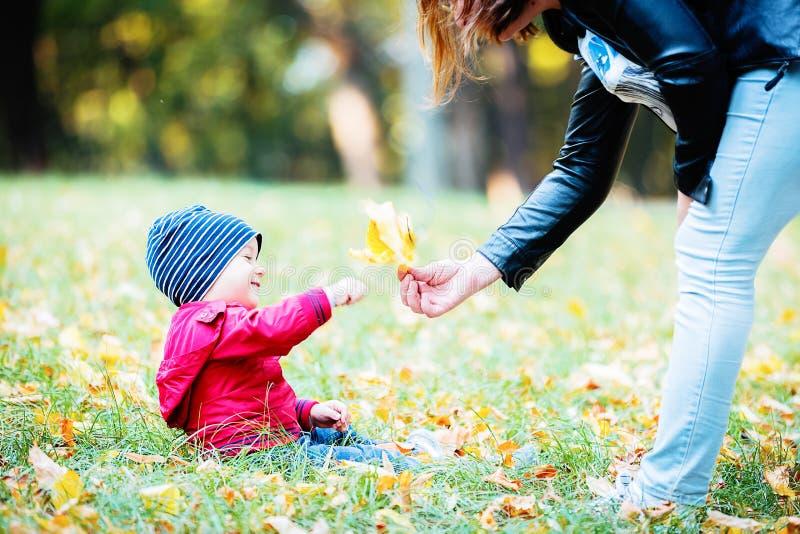 Dois anos de criança idosa têm o divertimento exterior no parque do outono fotos de stock royalty free