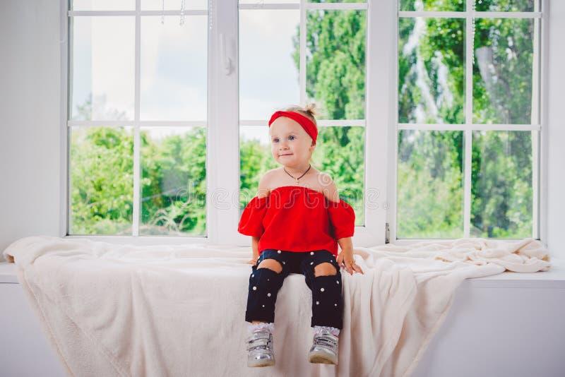 Dois anos pouco engraçados da criança idosa da menina na roupa e calças de brim e sapatilhas vermelhas à moda na soleira perto da fotografia de stock