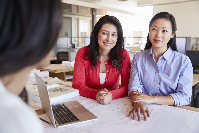 Dois arquitetos fêmeas na conversação com um colega imagem de stock