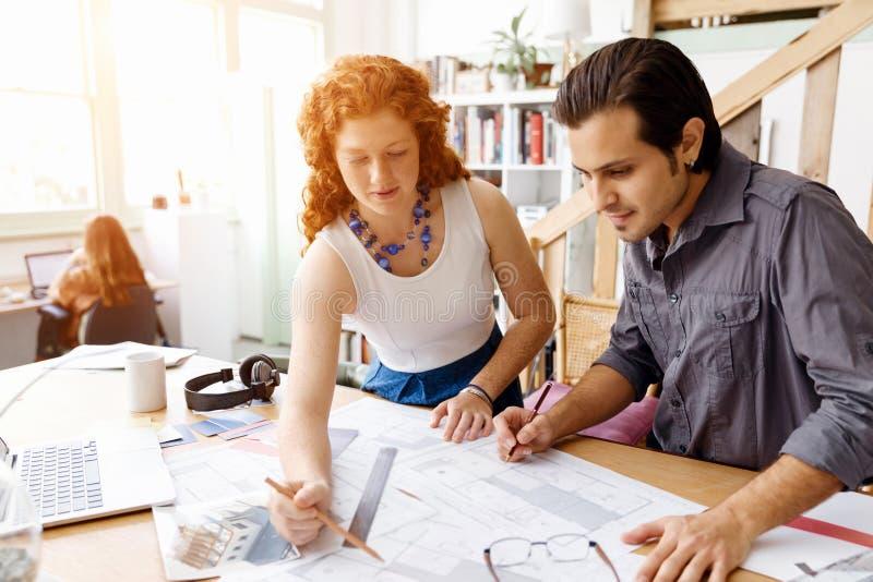 Dois arquitetos novos no escritório imagem de stock