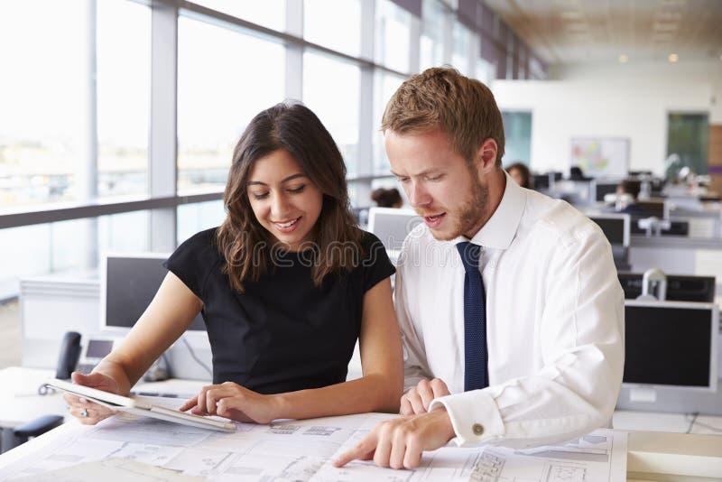 Dois arquitetos novos que trabalham junto em um escritório imagens de stock royalty free