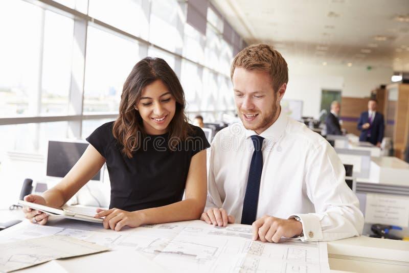 Dois arquitetos novos que trabalham junto em um escritório imagem de stock royalty free