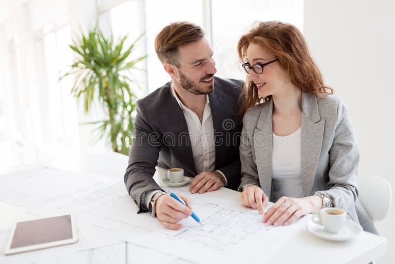 Dois arquitetos novos que trabalham junto no escritório fotografia de stock