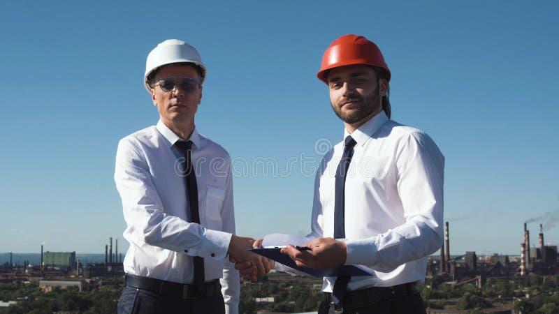 Dois arquitetos ou coordenadores masculinos novos fazem o negócio fotos de stock