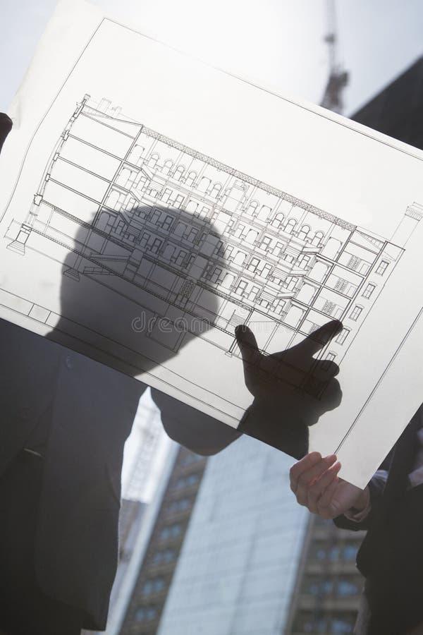 Dois arquitetos que olham o modelo no canteiro de obras imagem de stock