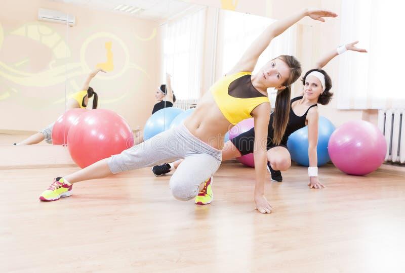 Dois atletas caucasianos fêmeas no bom ajuste que tem os braços que esticam exercícios fotos de stock