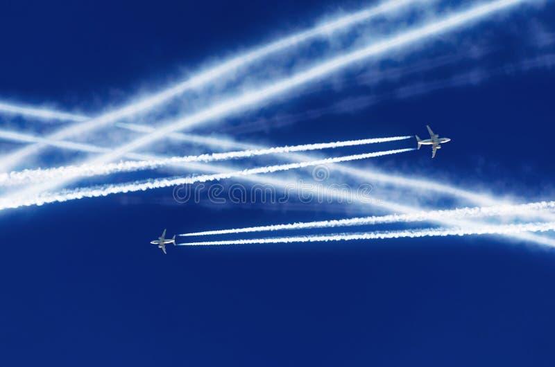 Dois aviões do passageiro encontrados na altura e foram cruzados por nuvens do contrail do aeroporto da aviação dos cursos fotos de stock