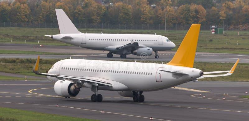 Dois aviões que apressam-se em uma pista de decolagem do aeroporto imagem de stock