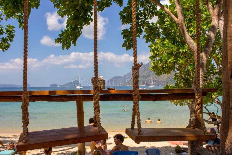 Dois balanços de suspensão no café exterior na praia Balanço da corda no litoral tropical Conceito exótico do curso Férias no par foto de stock royalty free