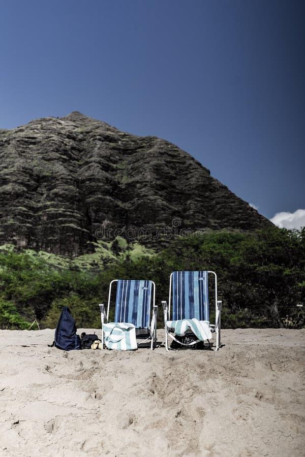 Dois bancos em uma praia com um monte pequeno no fundo fotografia de stock