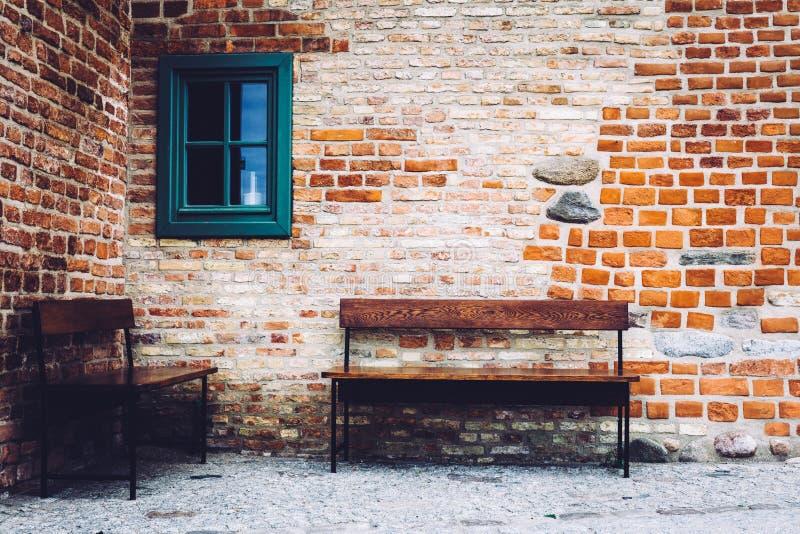 Dois bancos que estão na frente da construção velha com janela verde foto de stock royalty free