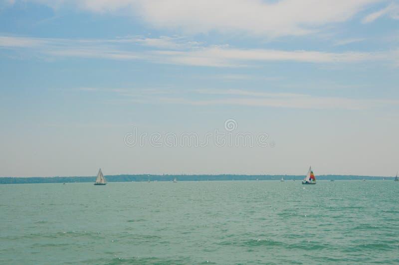 Dois barcos de navigação no primeiro plano sob o céu azul bonito com nuvens Competição da vela no lago Balaton, Hungria fotografia de stock royalty free