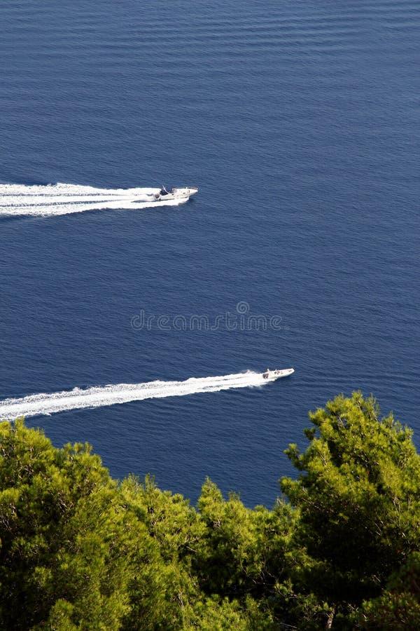 Dois barcos a motor contra um mar azul e árvores imagens de stock royalty free