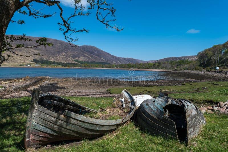 Dois barcos quebrados perto de um lago imagens de stock royalty free