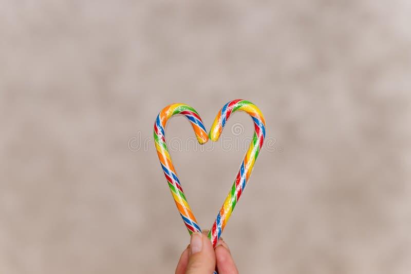 Dois bastões de doces que fazem um coração no fundo textured, coração do bastão de doces na mão fêmea Bastões de doces coloridos  foto de stock royalty free