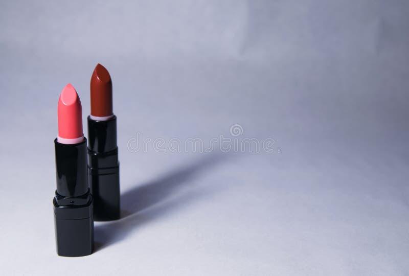 Dois batons do suporte da cor do rosa e da cenoura verticalmente em um fundo branco fotos de stock royalty free
