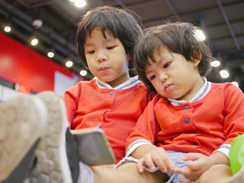 Dois bebê asiático pequeno, irmãs, sentando e olhando um smartphone junto, ao esperar sua mãe para fazer algumas tarefas imagem de stock royalty free