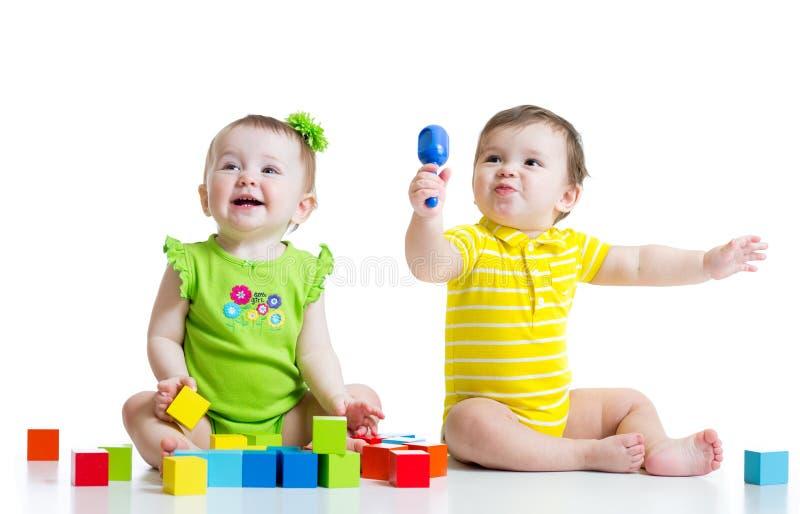 Dois bebês adoráveis que jogam com brinquedos toddlers imagens de stock royalty free