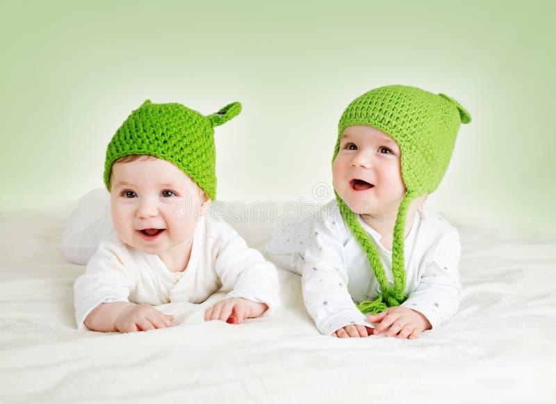 Dois bebês bonitos que encontram-se em chapéus da rã na cobertura do spft fotos de stock