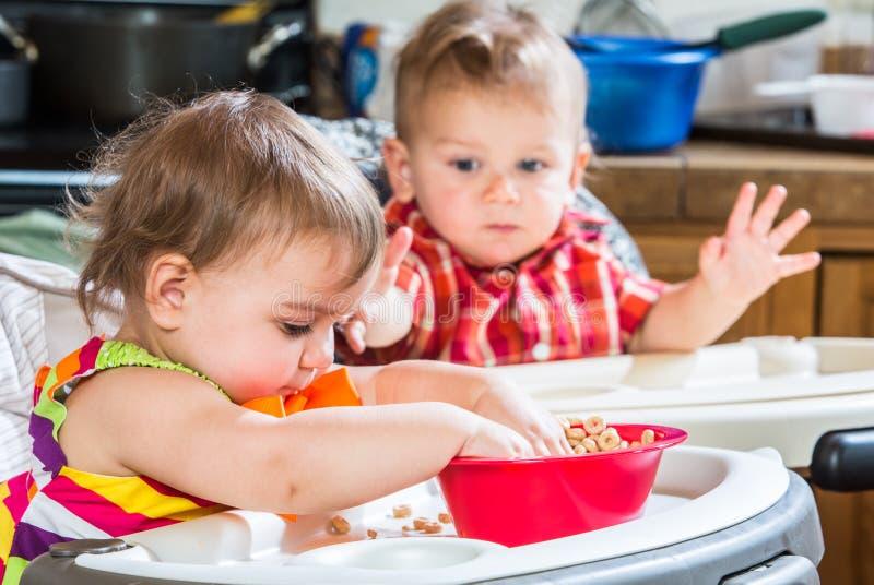 Dois bebês comem o café da manhã imagens de stock royalty free