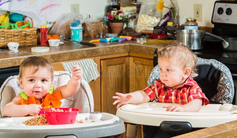 Dois bebês comem o café da manhã imagem de stock royalty free