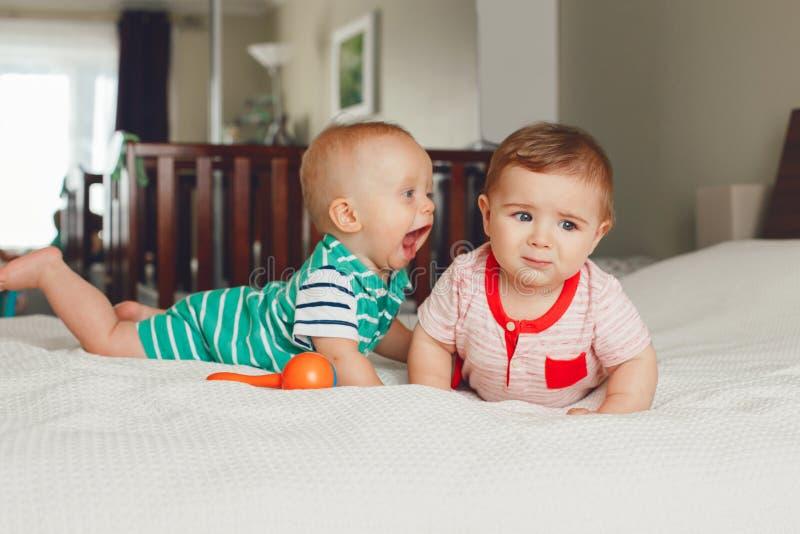 dois bebês engraçados adoráveis bonitos caucasianos brancos que encontram-se junto na cama que comunica-se e que joga foto de stock royalty free