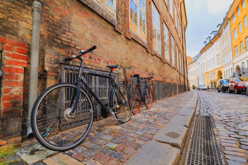 Dois bicycycles fechados na rua velha colorida da cidade de Copenhaga fotografia de stock