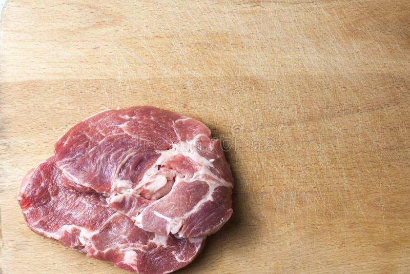 Dois bifes da carne de carne de porco, em uma placa de corte imagem de stock royalty free