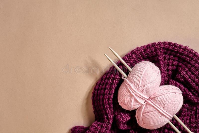 Dois bolas do fio para confecção de malhas, agulhas de confecção de malhas e e roxos cor-de-rosa fizeram malha a opinião superior foto de stock