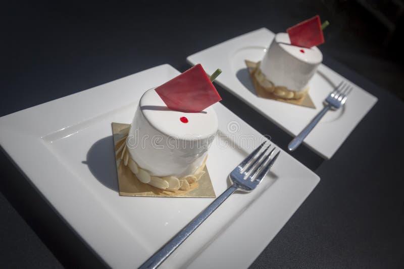 Dois bolos brancos com chocolate vermelho nas placas brancas em um café Fundo escuro imagem de stock