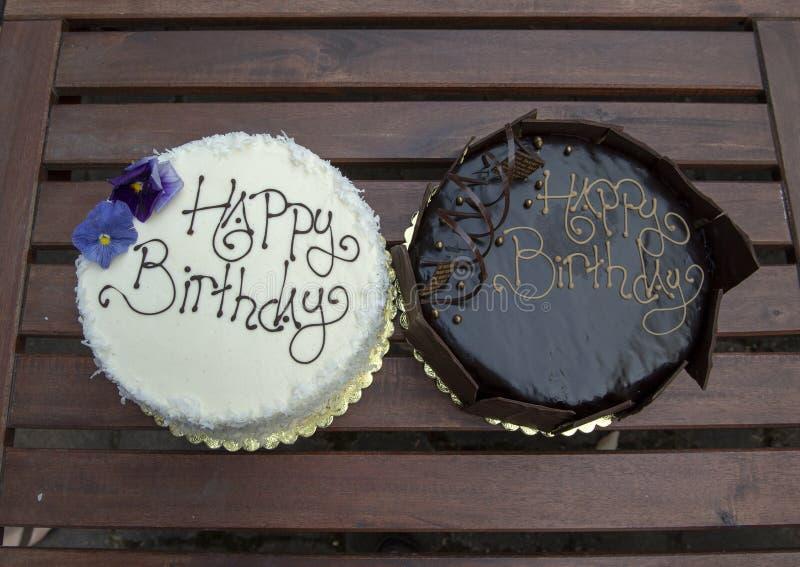 Dois bolos de aniversário, um chocolate e uma baunilha fotografia de stock royalty free