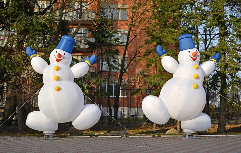 Dois bonecos de neve infláveis alegres Decoração do Natal na rua de Zelenogradsk, a região de Kaliningrad fotografia de stock royalty free