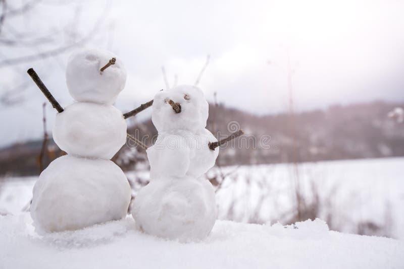 Dois bonecos de neve minúsculos, pequenos reais na natureza no dia nevado, frio nas montanhas fotografia de stock royalty free