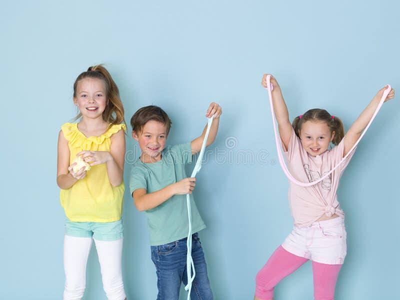 Dois bonitos e meninas engraçadas e um menino fresco que jogam com muito limo na frente do fundo azul e que têm muito divertiment imagem de stock royalty free